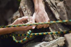 The climber holds his hand over the ledge of the cliff. Rock climber`s hand gripping small hold on natural cliff, shallow depth of field Royalty Free Stock Image