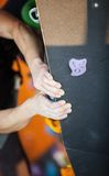 Rock climber's hands on artificial climbing wall. Indoors Royalty Free Stock Photography
