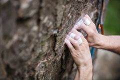 Rock climber`s hands gripping small hold on natural cliff. Closeup view Stock Images