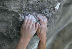 Rock climber's hands on handhold. His hands is covered in chalk. Shallow depth of field Royalty Free Stock Photography