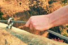 Rock climber's hands hold on steel twisted rope at steel bolt eye anchored in rock. Tourist path via ferrata. Stock Photo