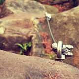 Rock climber's path on steel twisted rope at steel bolt eye anchored in rock.  Stock Photography