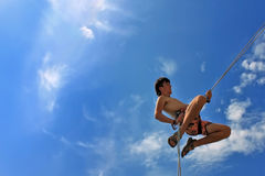 Rock climber on a safety rope. On blue sky background Stock Images