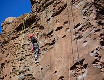 Basalt Rock Climber 2. A rock climber scaling a massive basalt pillar with the proper safety harnesses, ropes, and cords Royalty Free Stock Images