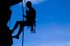 Rock climber silhouette. Silhouette of male rock climber hanging from ropes Stock Photo