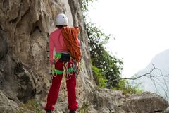 Rock climber standing in front of mountain cliff outdoor Royalty Free Stock Image