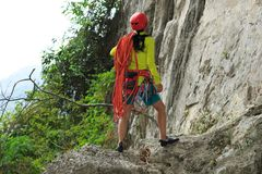 Rock climber standing with climbing gears and rope Royalty Free Stock Images