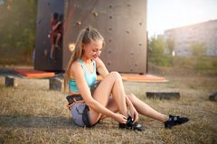 Rock climber strong woman putting on climbing shoes while sitting on grass. Pretty healthy slim girl prepares for Stock Photo
