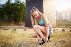 Rock climber strong woman putting on climbing shoes while sitting on grass. Pretty healthy slim girl prepares for Royalty Free Stock Image