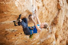 Rock climber struggling to make next movement up Stock Images