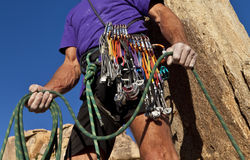 Rock climber on the summit. Male rock climber coils ropes on the top of a sheer cliff after a successful ascent Royalty Free Stock Image