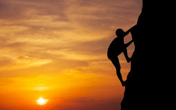 Rock climber at sunset background. stock image