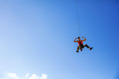 Rock climber swinging on rope and flexing muscles Royalty Free Stock Photo