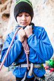A rock climber tie a knot for insurance. A rock climber tie a knot on a rope. A person is preparing for the ascent. The child learns to tie a knot. Checking the Stock Photos