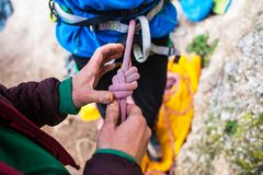 A rock climber tie a knot for insurance. A rock climber tie a knot on a rope. A person is preparing for the ascent. The child learns to tie a knot. Checking the Stock Photography