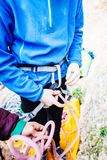 A rock climber tie a knot for insurance. A rock climber tie a knot on a rope. A person is preparing for the ascent. The child learns to tie a knot. Checking the Stock Image