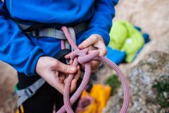 A rock climber tie a knot for insurance. A rock climber tie a knot on a rope. A person is preparing for the ascent. The child learns to tie a knot. Checking the Royalty Free Stock Images