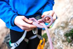 A rock climber tie a knot for insurance. A rock climber tie a knot on a rope. A person is preparing for the ascent. The child learns to tie a knot. Checking the Stock Photo