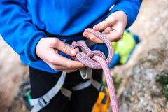 A rock climber tie a knot for insurance. A rock climber tie a knot on a rope. A person is preparing for the ascent. The child learns to tie a knot. Checking the Royalty Free Stock Photography