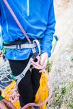 A rock climber tie a knot for insurance. A rock climber tie a knot on a rope. A person is preparing for the ascent. The child learns to tie a knot. Checking the Stock Images