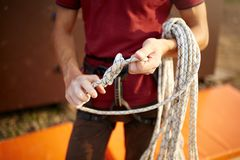 A rock climber tie a knot on a rope. A person is preparing for the ascent. Man learns to tie a knot near climbing wall. A rock climber tie a knot on a rope. A Royalty Free Stock Image