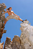 Rock climber on top looks far Stock Images