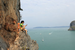 Rock climber use smartphone at seaside mountain cliff Royalty Free Stock Photos
