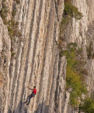 Rock climber on vertical difficult stone wall Stock Images