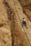 Rock climber works his way up a sheer cliff. SMITH ROCK STATE PARK, OREGON - MAY 20 - Rock climber works his way up a sheer cliff face on May 20, 2007, in Royalty Free Stock Photo