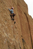 Rock climber works his way up a sheer cliff. SMITH ROCK STATE PARK, OREGON - MAY 20 -Rock climber works his way up a sheer cliff face on May 20, 2007, in Central Royalty Free Stock Photography