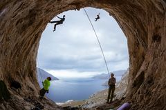 Rock climbers in cave: belayers watching leading climbers Stock Photo