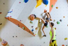 Young woman climbing bouldering problem route, male instructor Stock Images