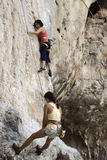 Rock climbers climbing the wall on Phra Nang beach Stock Photos