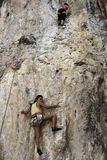 Rock climbers climbing the wall on Phra Nang beach Royalty Free Stock Images