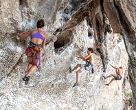 Rock climbers climbing the wall on Railay beach. Royalty Free Stock Images