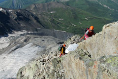 Rock climbers in helmets on rocky mountain route Stock Images