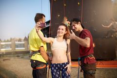 Rock climbers insure each other at artificial climbing wall making a selfie with smartphone outdoors. Sporty men amd. Rock climbers insure each other at Stock Photography