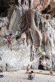 Rock climbers and tourists on Railay beach. Royalty Free Stock Images