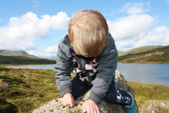 Rock climbing. Little boy sitting on a rock and drawing with his nails Royalty Free Stock Images