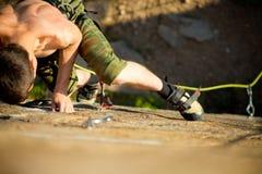 Rock climbing. Young rock climber climbs the cliff with a belay royalty free stock photos
