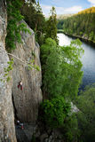Rock Climbing. A male climber against a large rock face climbing lead against a magnificant landscape Royalty Free Stock Images