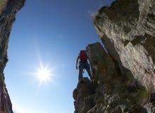 Rock-climbing. Terrific view of a climbing route: climber standing on the rocky ridge, back-light, fish-eye lens Stock Image