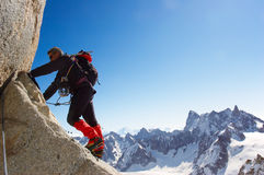 Rock-climbing. Climber climbing a rocky wall; horizontal frame. Aiguille du Midi, Mont Blanc massif, Chamonix, France. In background the north face of Grand Stock Image