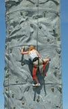 Rock Climbing. Girl climbing a rock wall royalty free stock photography