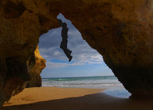 Rock climbing at Algarve. Shadow man hanging from a cliff at the famous algarve coast, Portugal Stock Photography