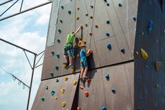 Rock climbing on an artificial rise. The boy climbs on the wall in an extreme park royalty free stock image