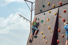 Rock climbing on an artificial rise. The boy climbs on the wall in an extreme park royalty free stock photography