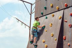Rock climbing on an artificial rise. The boy climbs on the wall in an extreme park stock image