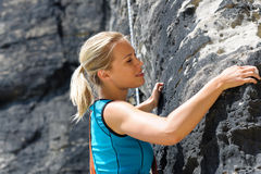 Rock climbing blond woman on rope Stock Photo