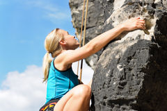 Rock climbing blond woman on rope sunny royalty free stock photography